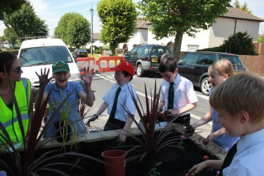 Local children help planting up one of the new planters installed a week ago on Norbury Avenue